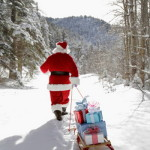 Santa Claus pulling sled with presents in snow